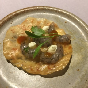 okoy-inspired plate, with fermented shrimp cracker topped with tamarind wood-smoked shrimps, ginger crème fraiche and soy gel